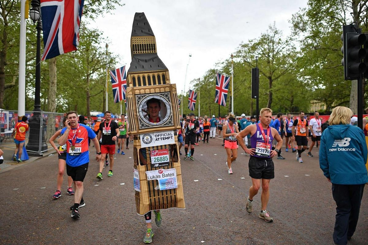 A runner in fancy dress mixes with other runners recovering after running the 2019 London Marathon in central London on April 28, 2019.