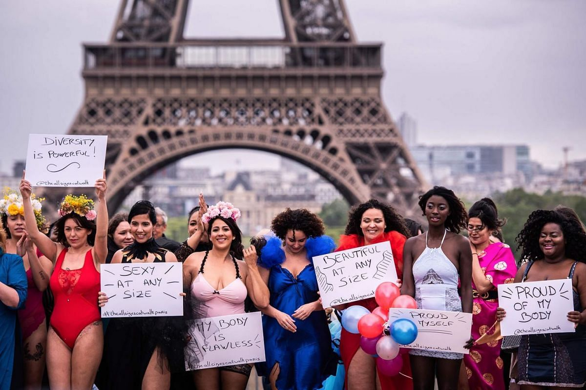 Models pose with placards in front of the Eiffel Tower during The All Sizes Catwalk event in Paris on April 28, 2019. About 40 women of different body shapes gathered for the event to promote self-acceptance.