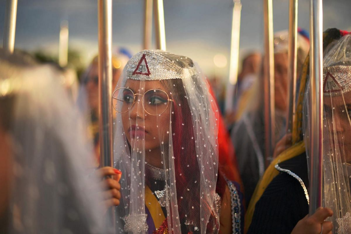 Female devotees of the Vale do Amanhecer religious community pray during their biggest ceremony of the year at a temple complex in Vale do Amanhecer, Brazil, on May 1, 2019.