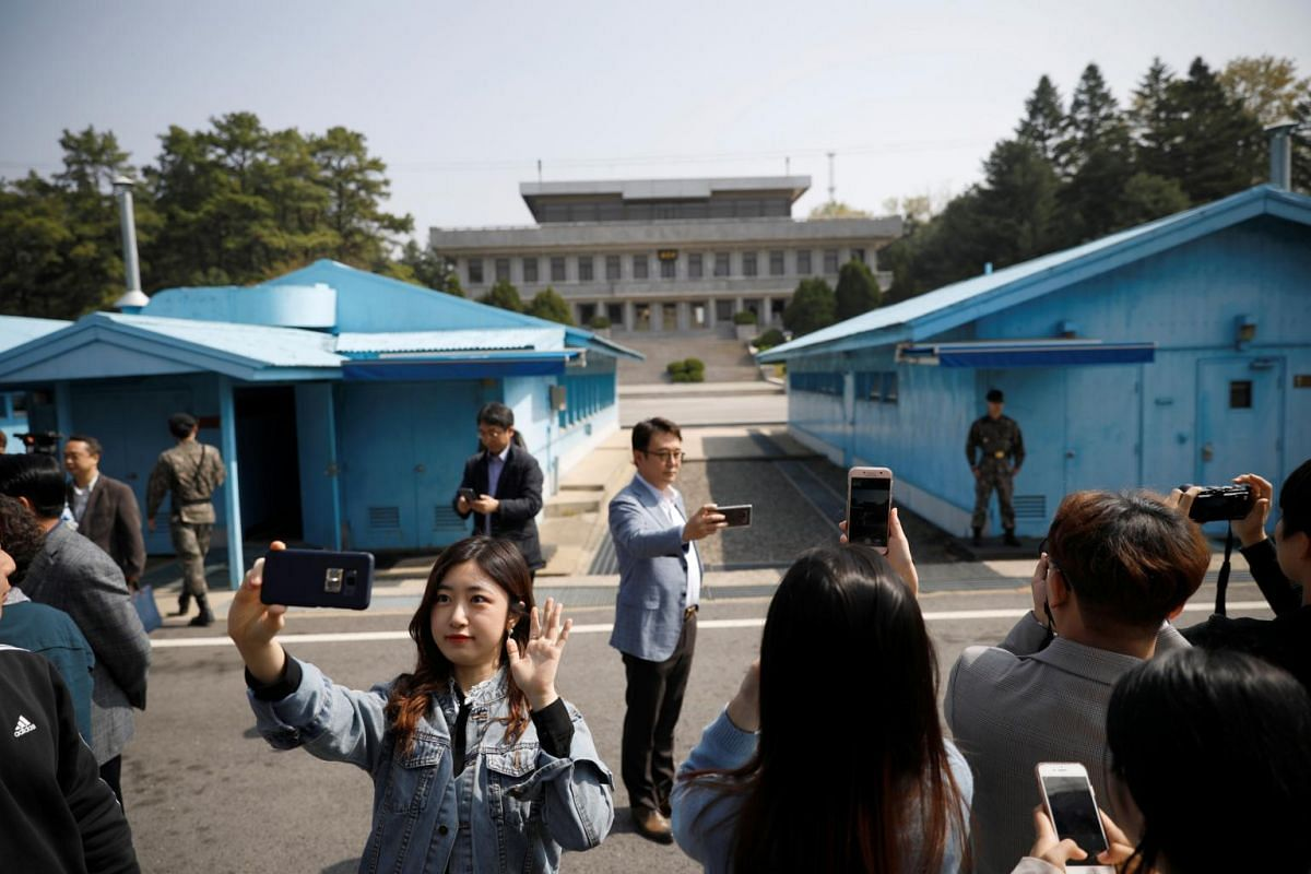 South Koreans take selfies as they tour the truce village of Panmunjom inside the Demilitarised Zone separating the two Koreas, on, May 1, 2019.