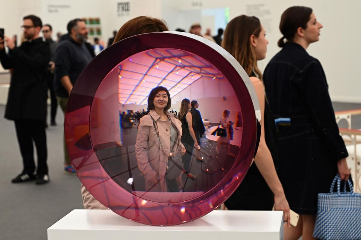 A woman reflected in Fred Eversley's art exhibit Untitled (Rose Mist) during Frieze New York 2019 art show, at Randall's Island Park, on May 2, 2019.