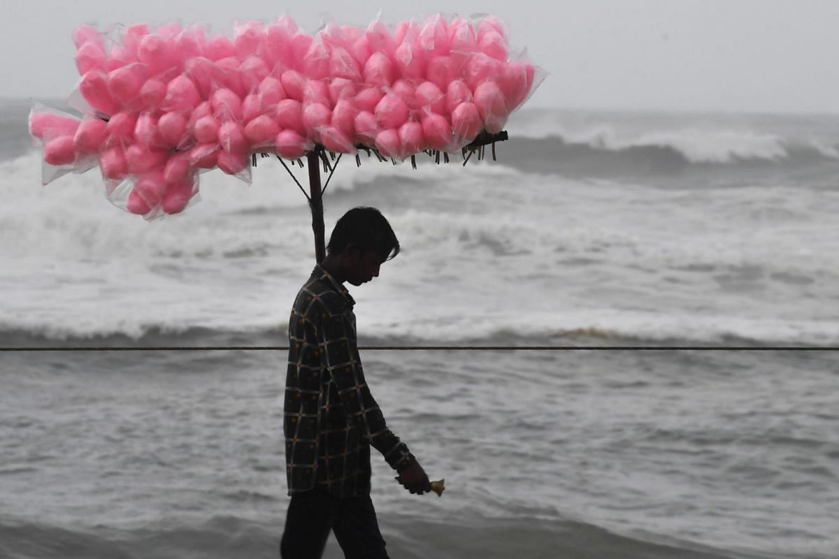 A candy vendor walks along a closed beach in Puri, in the eastern Indian state of Odisha, on May 2, 2019, as cyclone Fani approaches the Indian coast.