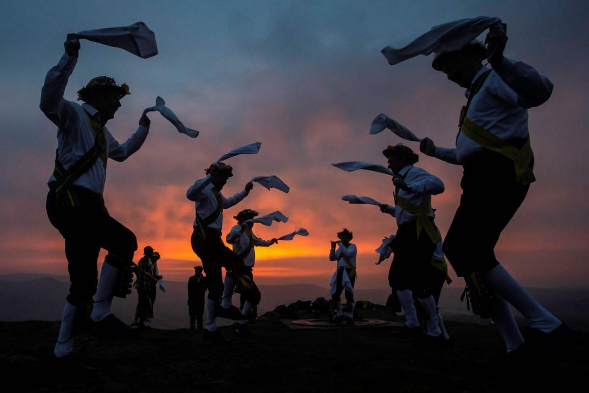 Members of the Chapel-en-le-Frith Morris Dancers dance atop the Eccles Pike at High Peak in Derbyshire, England, before sunrise, on May 1, 2019.