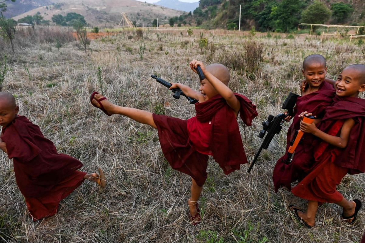 Buddhist novices play with toy guns during the rocket festival in Nantar, Shan state, Myanmar, on April 28, 2019.
