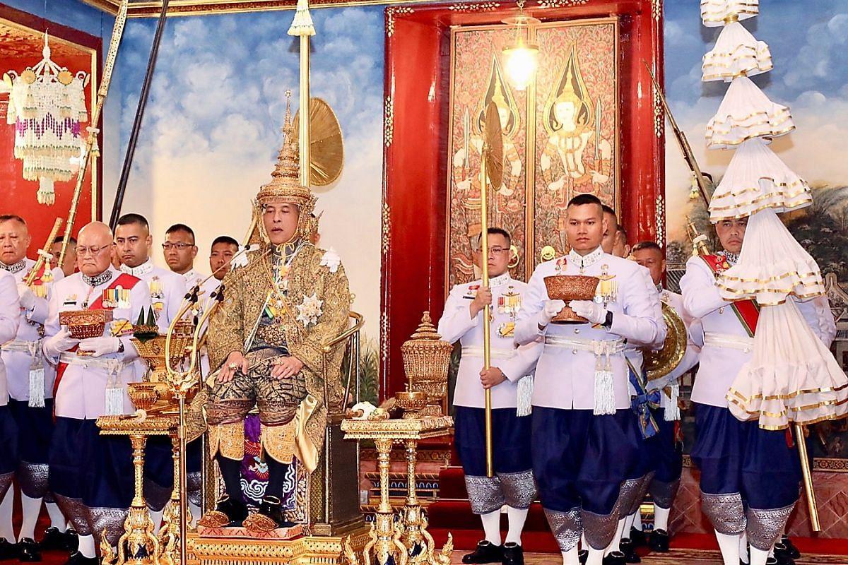 Thai King Maha Vajiralongkorn wearing a crown while sitting on the throne during his coronation ceremony at the Grand Palace in Bangkok.