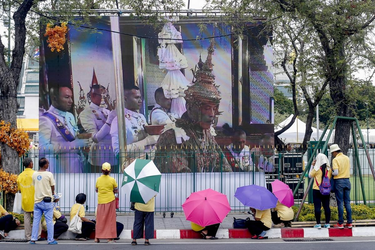 People watching the coronation ceremony of Thai King Maha Vajiralongkorn outside the Grand Palace in Bangkok on May 4, 2019.
