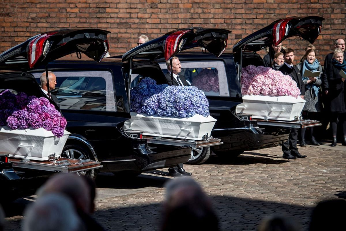 People stand by caskets at the funeral service for the three children of CEO of clothing brand Bestseller, Anders Holch Povlsen, who were victims of a string of suicide bomb attacks in Sri Lanka on April 21, at the Aarhus Cathedral in Aarhus, Denmark