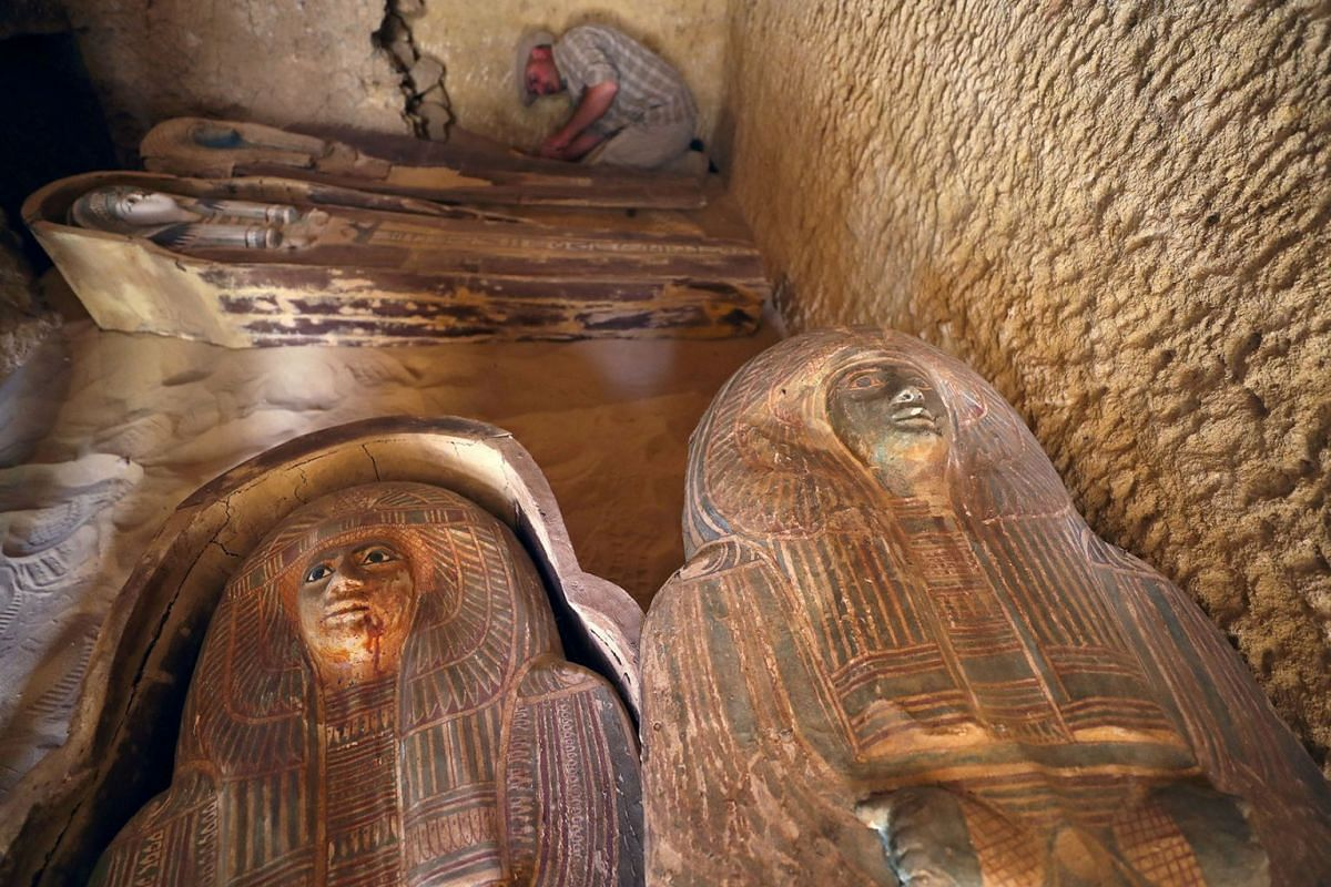 An Egyptian archaeologist works on the sarcophagi at the newly discovered burial site, the Tomb of Behnui-Ka and Nwi, dating back to circa 2500 B.C. near the Great Pyramids in Giza, on the outskirts of Cairo, Egypt May 4, 2019. PHOTO: REUTERS
