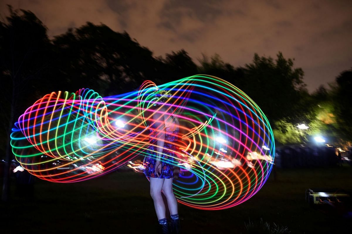 A woman dances with light at an event event called 'Catharsis on the Mall' in Washington, U.S., May 4, 2019. PHOTO: REUTERS