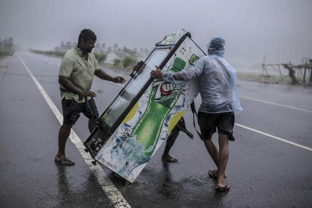 People carry a fridge across a highway during Cyclone Fani in the Puri district of Odisha, India, on May 3, 2019.