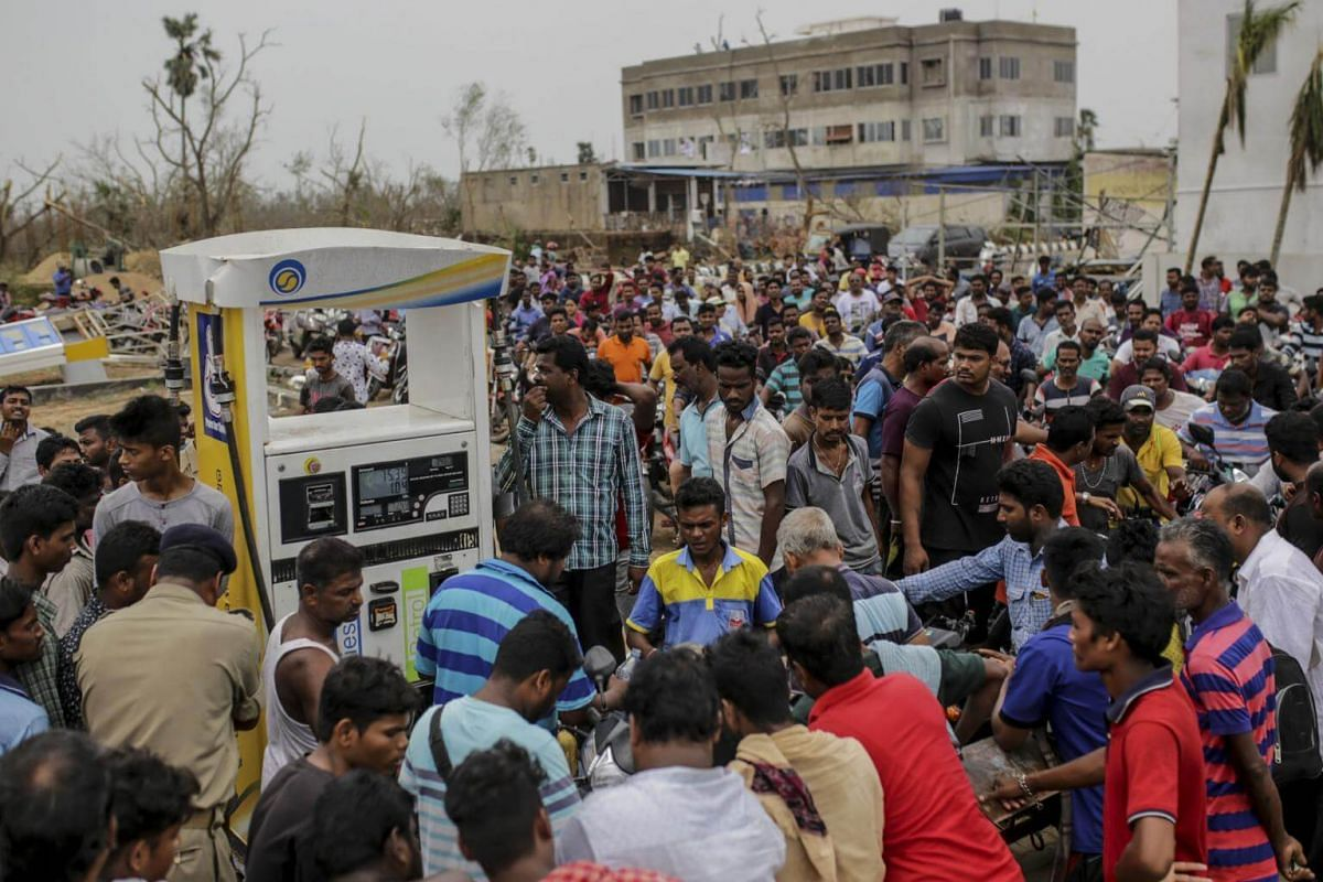 Motorcyclists wait in a queue at a gas station in Puri, India, on May 5, 2019.