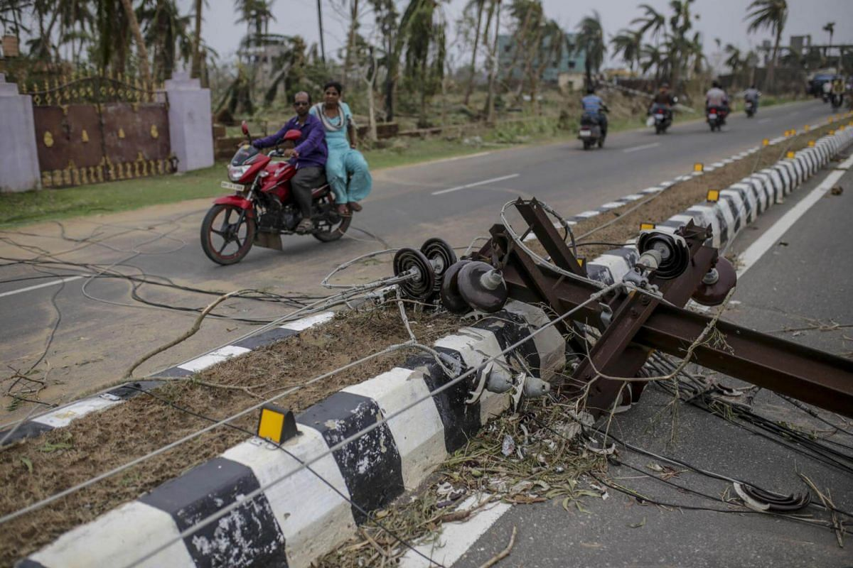 A motorcyclist drives past a damaged electrical pole in Puri, India, on May 5, 2019.