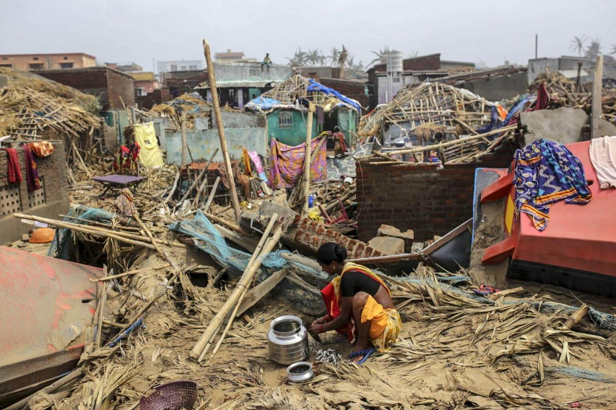 A woman prepares food in front of damaged homes after Cyclone Fani hit Puri, India, on May 4, 2019.