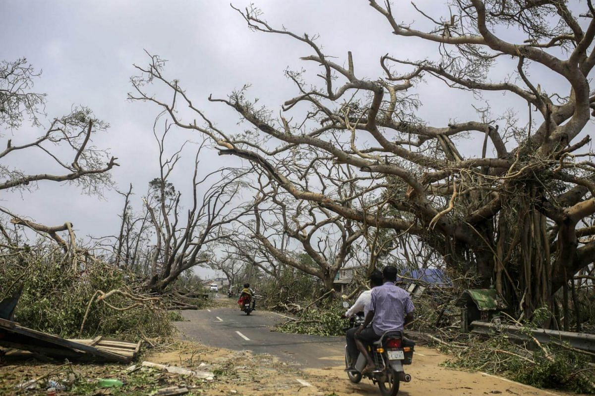Motorcyclists travel past damaged trees after Cyclone Fani hit Puri, India, on May 4, 2019.