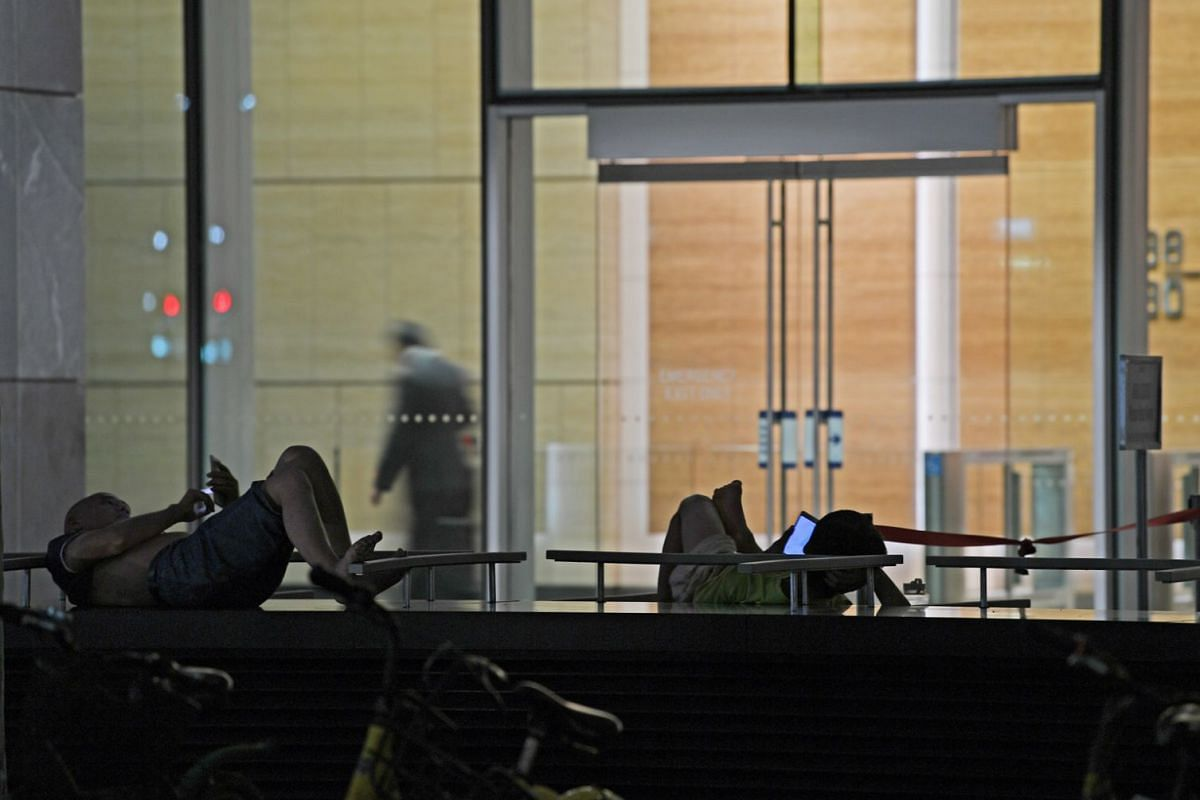 Foreign workers lounging outside Marina Bay Financial Centre's Tower 3, engaged with their mobile devices.