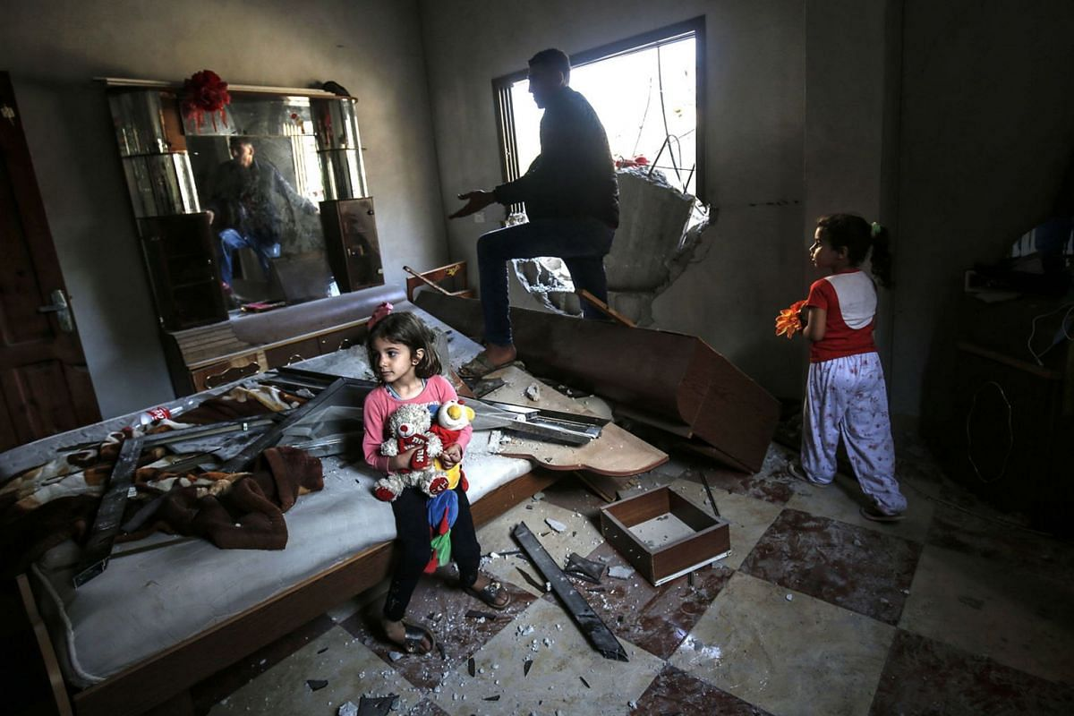 Young girls and a man gather among debris and shattered glass in a room that was hit during an Israeli air strike on Rafah in the southern Gaza strip on May 5, 2019. PHOTO: AFP
