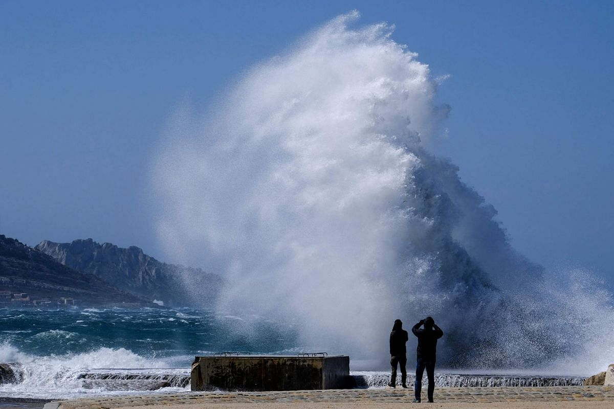 People watch heavy waves hiting the shore at the Plage du David beach in downtown Marseille, as storm Eleanor hits southern parts of France on May 5, 2019. PHOTO:  AFP