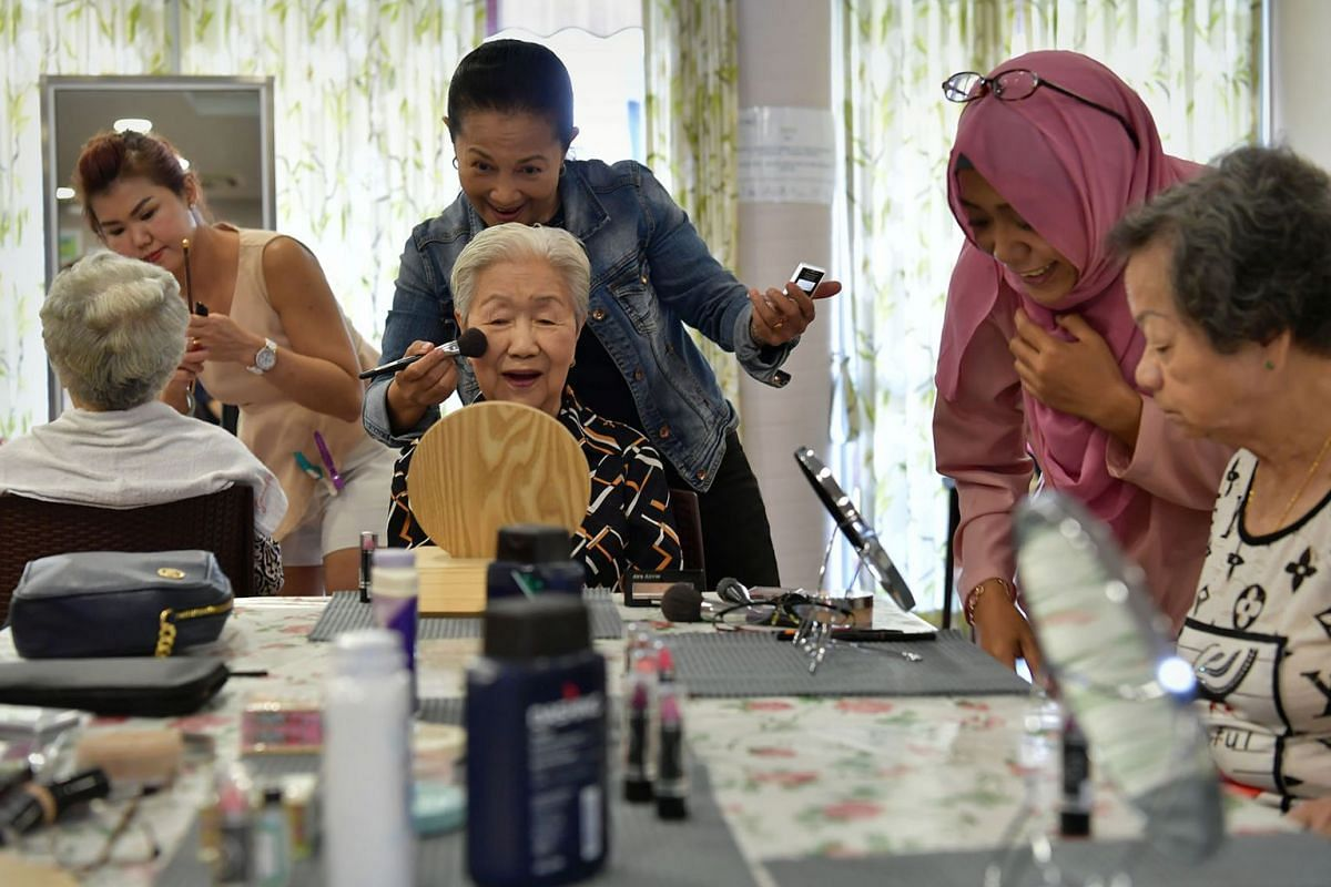 Madam Tay Ah Lay (centre), 83, and other Heritage Trunks programme participants having their make-up done by volunteer stylists, May 6, 2019. In the programme, launched by the National Heritage Board in collaboration with St Luke's ElderCare, theme