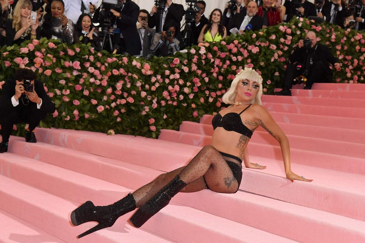 Pop star Lady Gaga sheds her bright pink dress to reveal three outfits layered underneath, including a bra and underwear, at the Met Gala at the Metropolitan Museum of Art, on May 6, 2019.