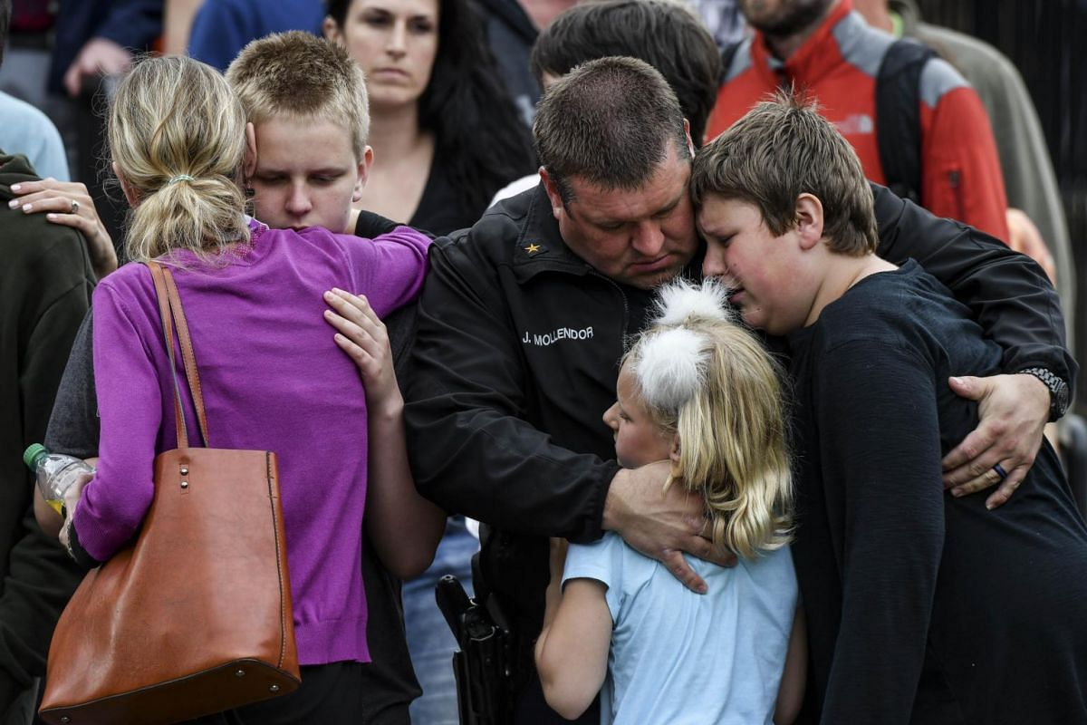 A police officer hugging his children after they were evacuated to the Northridge Recreation Centre in Highlands Ranch, Colorado.