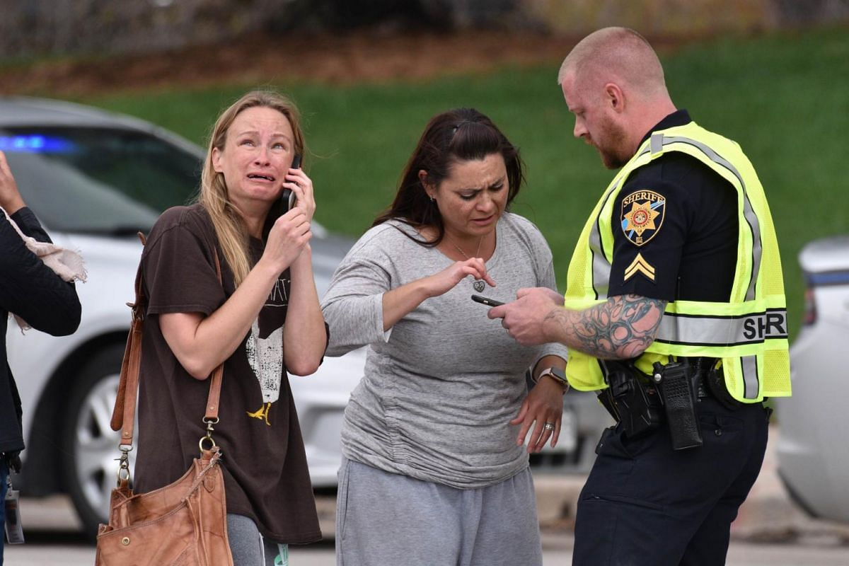 Parents speaking to a police officer after the shooting at STEM School Highlands Ranch.