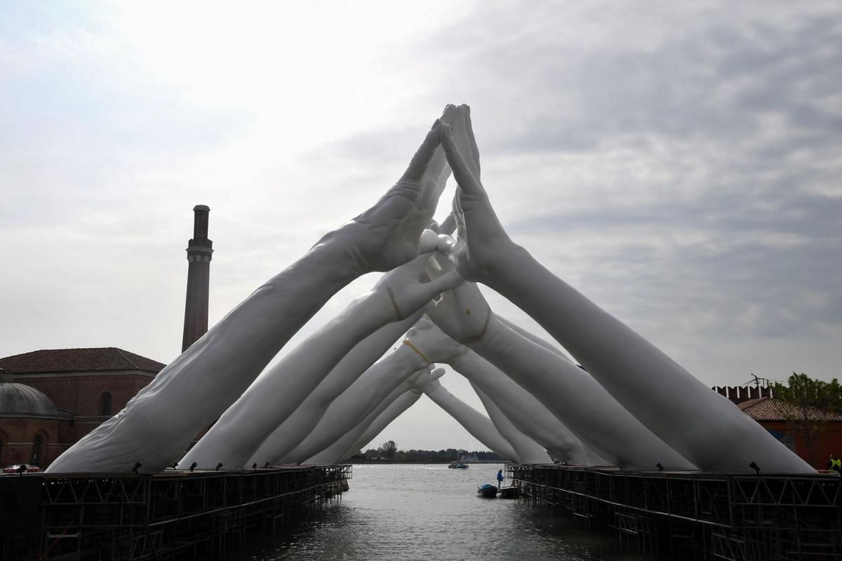 A view of Building Bridges by Italian artist Lorenzo Quinn - a sculptural installation showing six pairs of arching hands creating a bridge over a Venetian waterway in the Arsenale former shipyard - ahead of the 58th International Art Exhibition of t