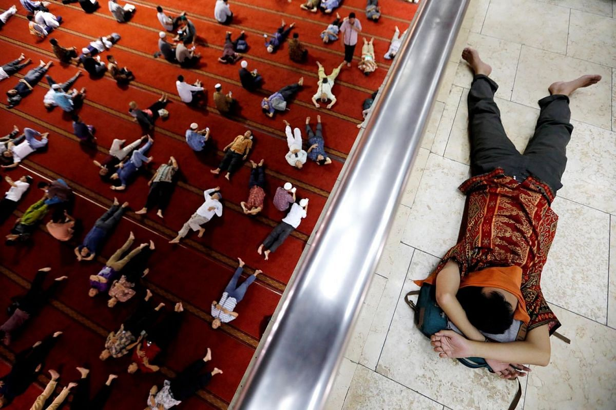 Muslim men take a rest after attending Friday prayers during the holy fasting month of Ramadan at Istiqlal mosque in Jakarta, Indonesia, May 10, 2019.