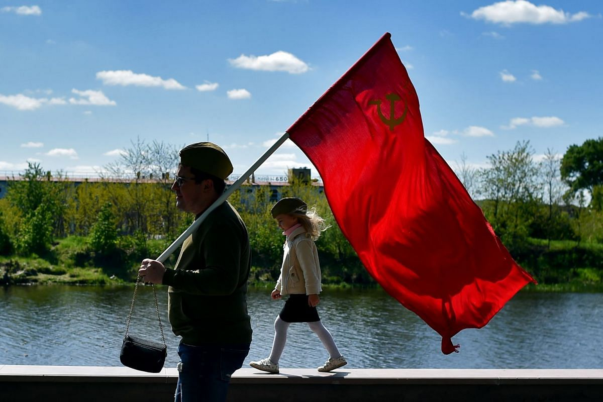 A man carries a Soviet flag during Victory Day celebrations in the town of Pinsk, some 305 km southwest of Minsk, Belarus, on May 9, 2019.