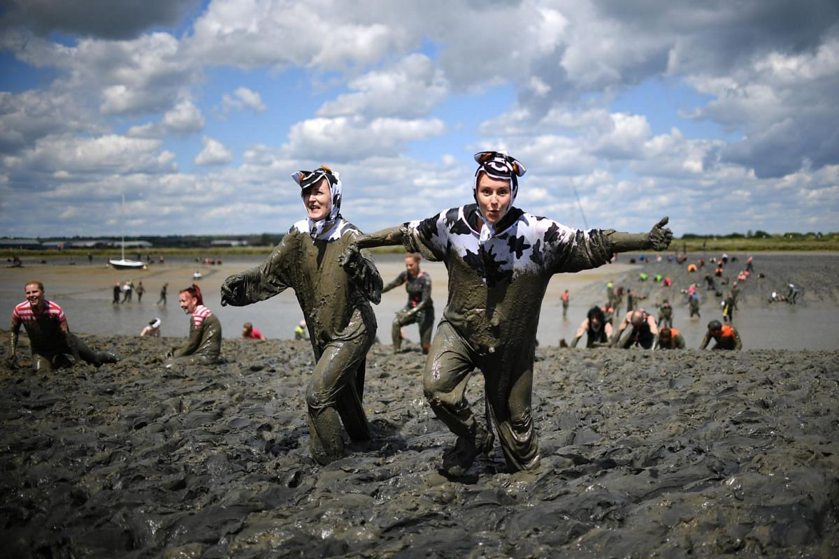 Two women in costumes take part in the annual Maldon Mud Race at Promenade Park, in Essex, England, where participants have to crawl through the bed of the River Blackwater, on May 12, 2019.