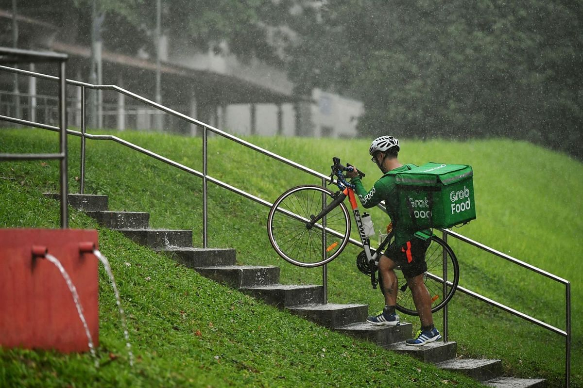 Even as heavy rain pelted Singapore, this GrabFood rider, struggling up the stairs near Guangyang Secondary School in Bishan, May 13, 2019, had to brave the weather to drop off food orders. PHOTO: THE STRAITS TIMES/LIM YAOHUI
