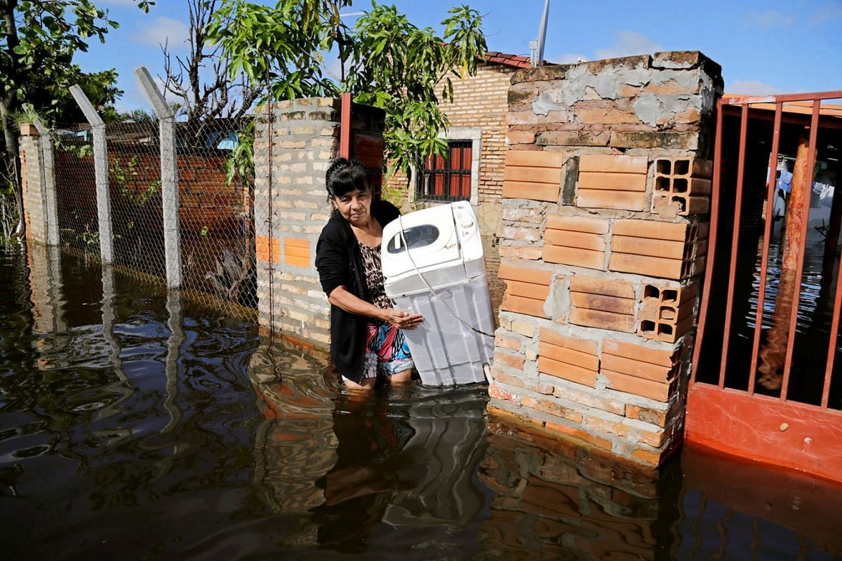A woman carries her belongings in a flooded street, after heavy rains caused Paraguay River to overflow, in a neighbourhood on the outskirts of Asuncion, Paraguay May 13, 2019. PHOTO: REUTERS