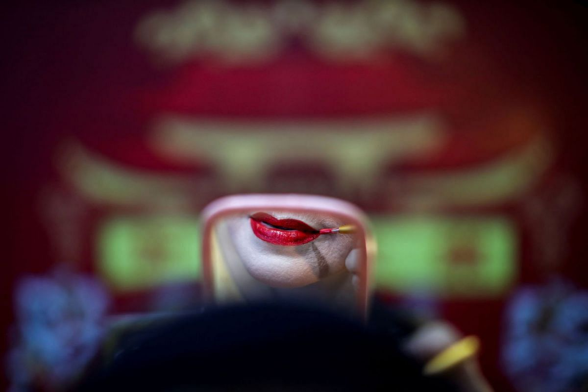 A member of a Chinese opera troupe applies make-up before performing at a shrine in Bangkok, Thailand, May 13, 2019. PHOTO: REUTERS