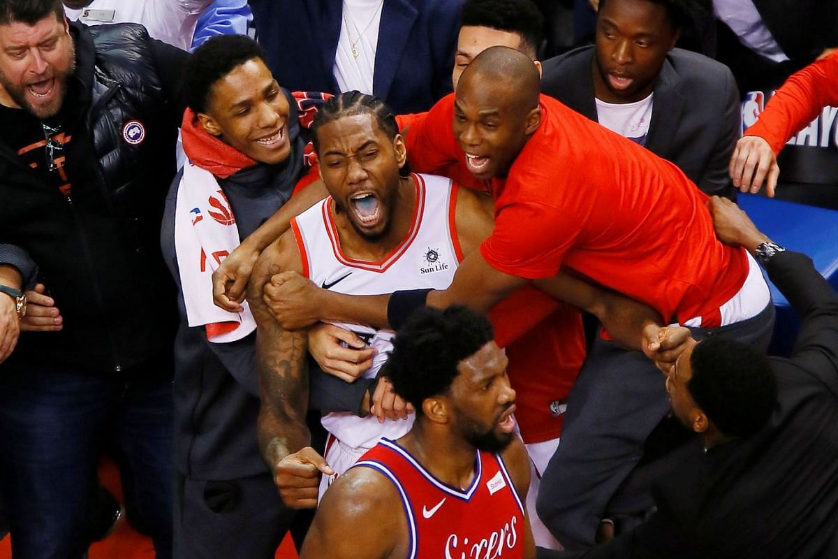 Toronto Raptors forward Kawhi Leonard (middle) is congratulated after making the game winning basket against Philadelphia 76ers center Joel Embiid (21) during game seven of the second round of the 2019 NBA Playoffs at Scotiabank Arena on May 12, 2019