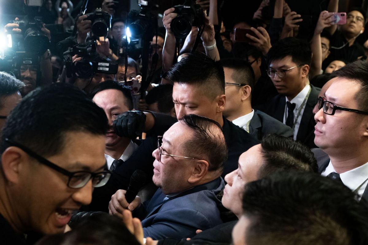 Pro-Beijing lawmaker Abraham Shek (centre, wearing glasses) being escorted by security guards at Hong Kong's Legislative Council on May 14, 2019.