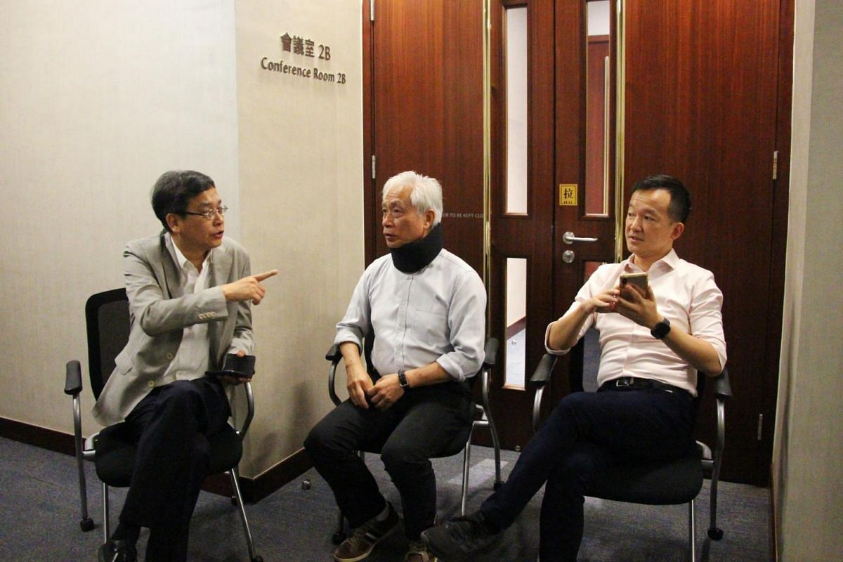 (From left) Pro-democracy legislators Ip Kin Yuen, Leung Yiu Chung and Raymond Chan Chi Chuen guard the entrance of the conference room in Hong Kong's legislature to prevent pro-Beijing counterparts from holding a parallel meeting to debate the extra