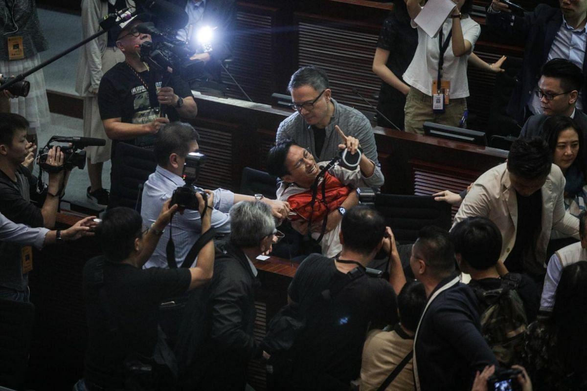 Pro-democracy lawmaker Eddie Chu Hoi Dick (centre) is restrained as chaos breaks out between opposing sides at the Legislative Council in Hong Kong on May 11, 2019.