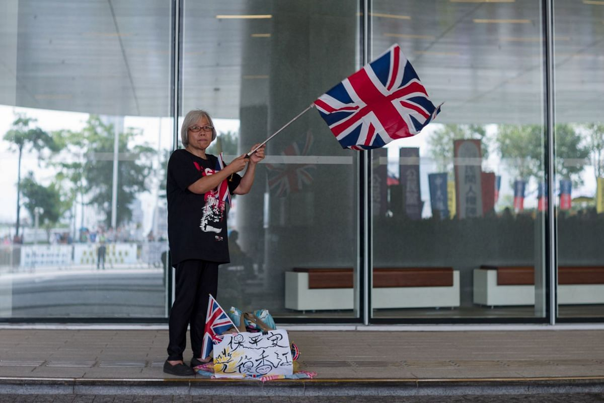 A pro-democracy supporter waves the Union Jack flag during a protest against planned extradition laws outside the Legislative Council in Hong Kong on May 14, 2019.