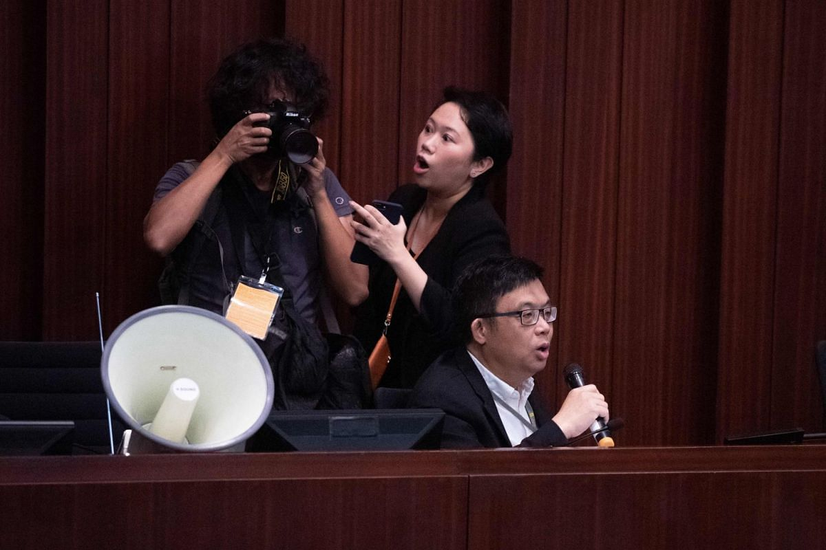 A photojournalist being urged to leave the conference room by Legislative Council staff as pro-democracy lawmaker James To speaks on extradition laws on May 14, 2019.