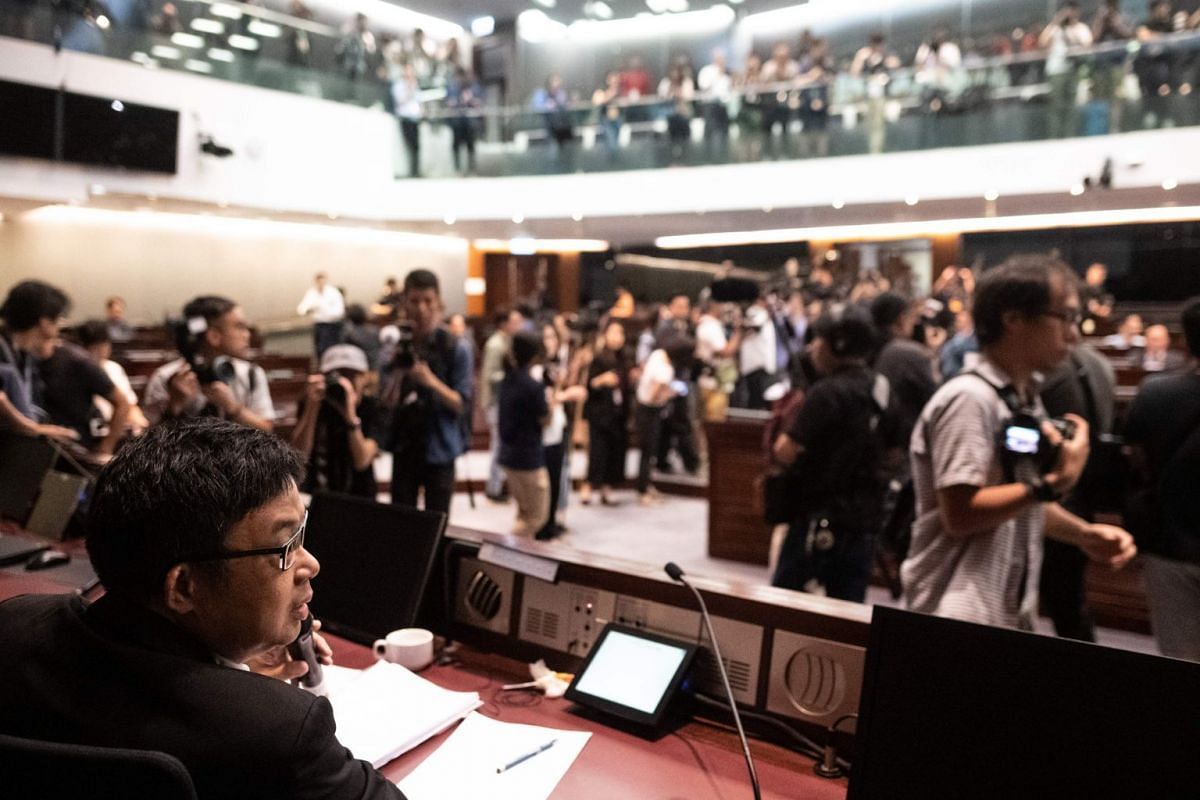 Pro-democracy lawmaker James To (left) attempts to talk about the controversial extradition laws as chaos breaks out inside the conference room at Hong Kong's Legislative Council on May 14, 2019.