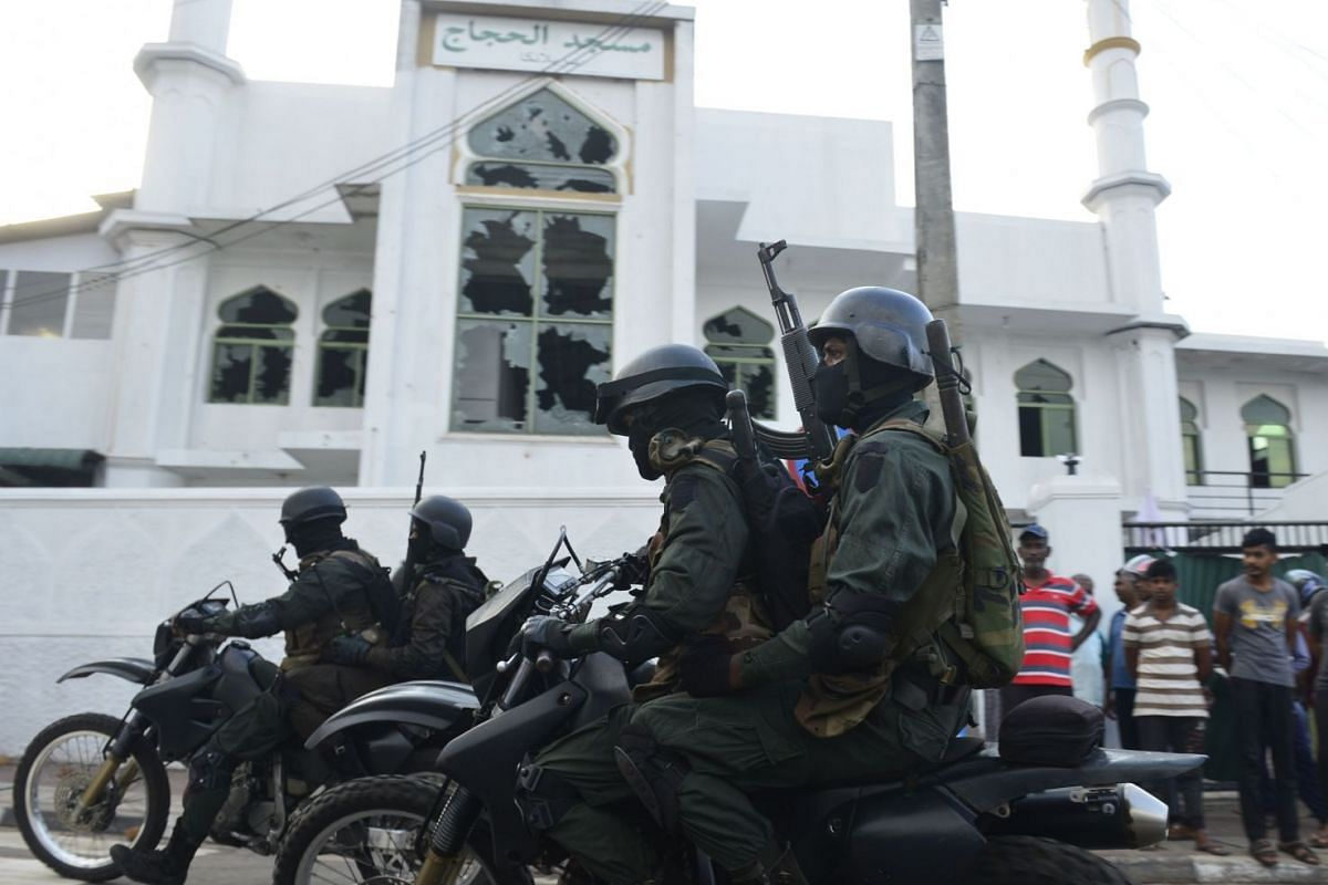 Heavily armed Sri Lankan soldiers ride on motorcycles in front of the Jumha Mosque after a mob attack in Minuwangoda on May 14, 2019.