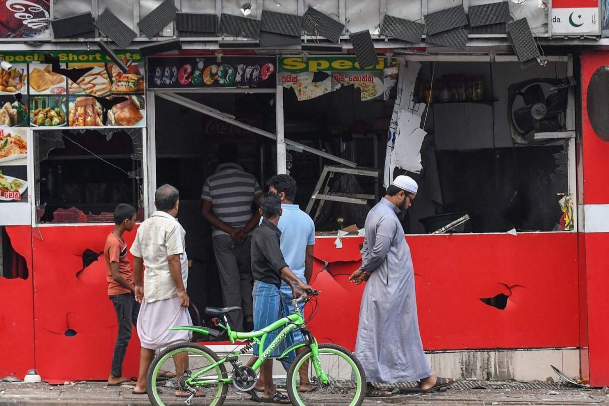 Passers-by at a badly damaged shop after a mob attack in Minuwangoda, Sri Lanka on May 14, 2019.