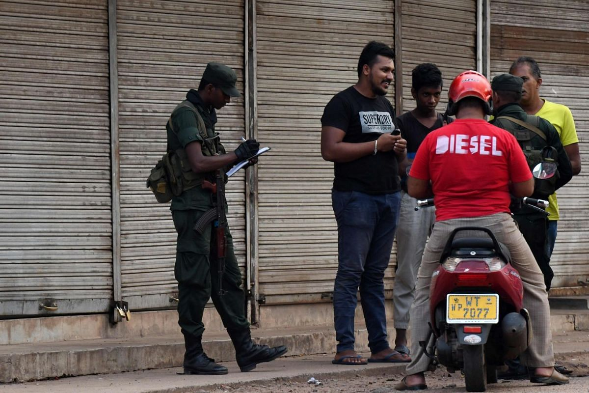Sri Lankan security personnel inspect a motorcycle at a roadside checkpoint in Minuwangoda on May 14, 2019.
