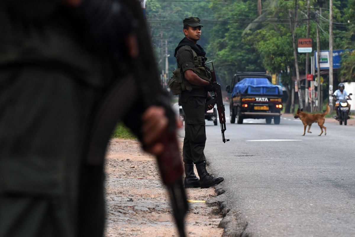 Sri Lankan security personnel stand guard at a roadside checkpoint in Minuwangoda on May 14, 2019.