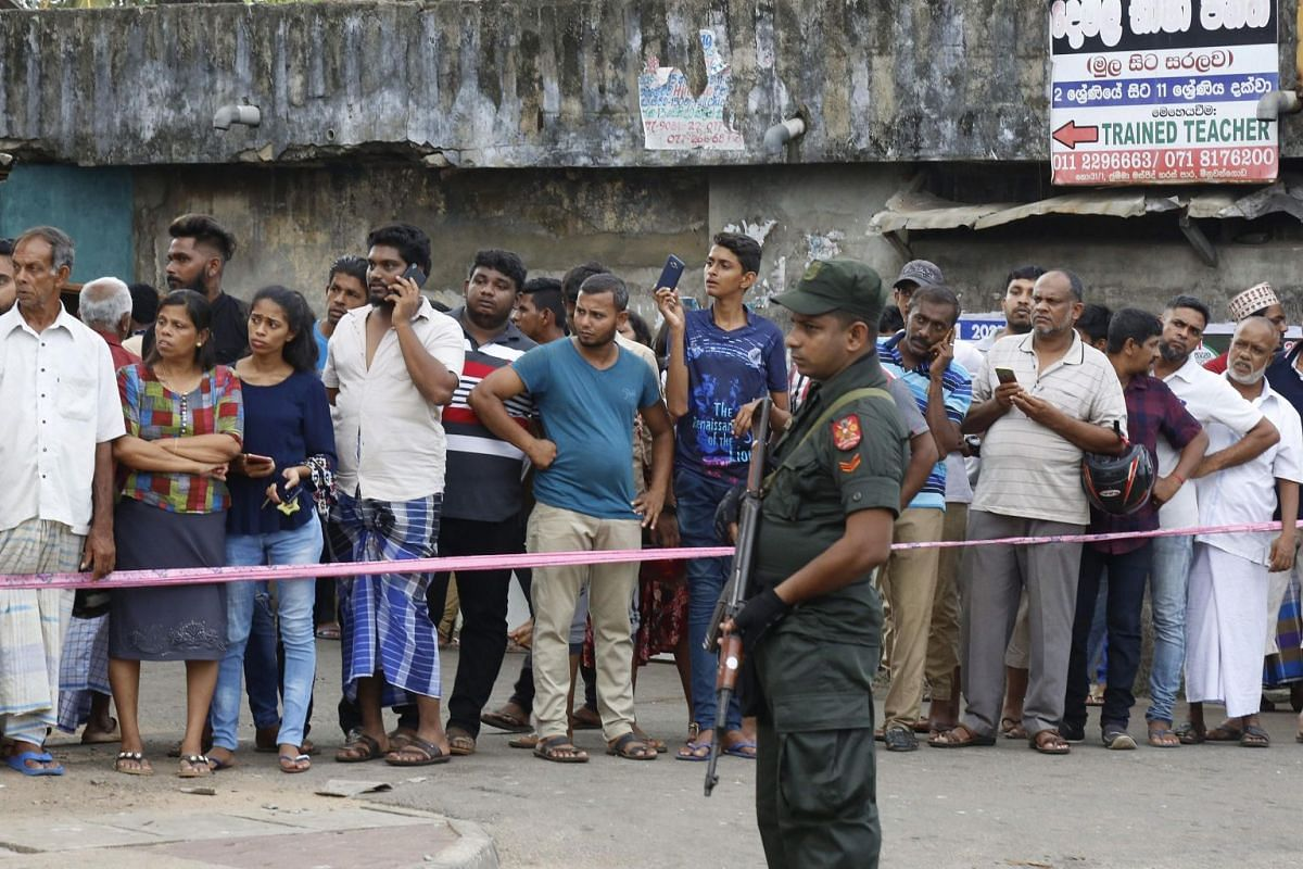 Locals look on as an area is cordoned off after sectarian clashes in Minuwangoda, 45km from Sri Lanka's capital, Colombo, on May 14, 2019.