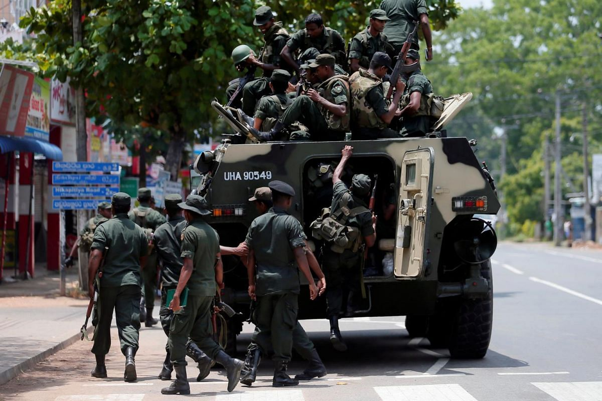 Sri Lankan soldiers prepare to patrol a road after a mob attack at a mosque in Hettipola, Sri Lanka on May 14, 2019.