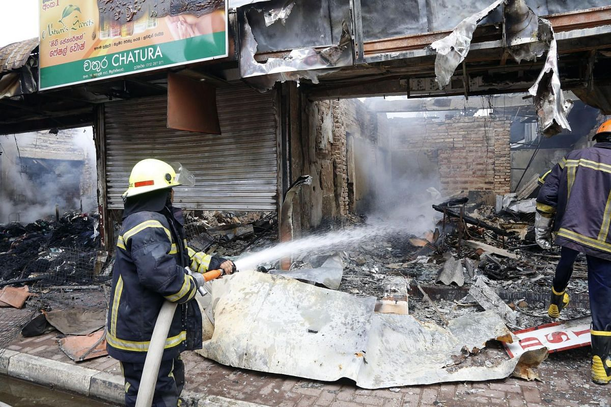 Sri Lankan firemen douse a fire at a shop after sectarian clashes in Minuwangoda on May 14, 2019.