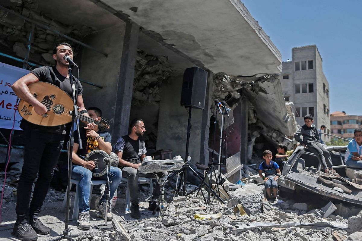 Members of the Palestinian band Dawaween perform during a musical event calling for a boycott of the Eurovision Song Contest hosted by Israel, on the rubble of a building that was recently destroyed by Israeli air strikes, in Gaza City on May 14, 201