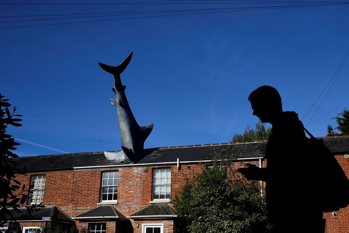 A man walks past a fibreglass sculpture 'Untitled 1986', but more commonly named 'The Headington Shark', which has been on display since 1986, embedded in the roof of a house in Oxford, Britain, May 14, 2019. PHOTO: REUTERS