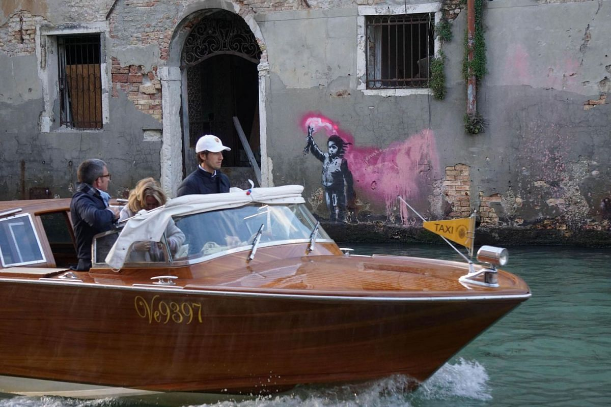 A motorboat passes in front of an alleged work of British street artist Banksy 'The shipwrecked child', that appeared on the outer wall of a house overlooking the canal Rio de Ca Foscari in Venice, Italy, 14 May 2019. PHOTO: EPA-EFE