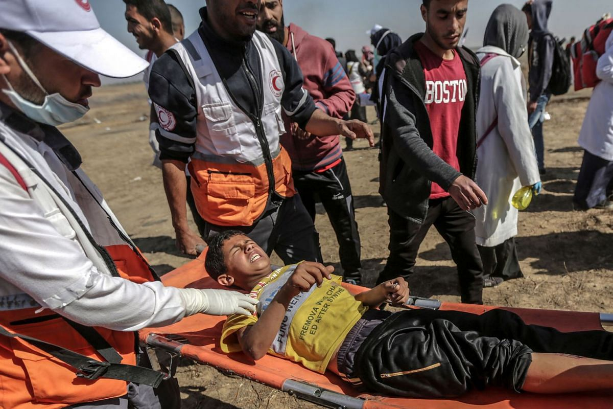 Palestinians carry a wounded boy during the clashes near the border between Israel and eastern Gaza Strip, 15 May 2019. PHOTO: EPA-EFE